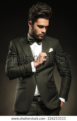 Handsome business man fixing his tuxedo while looking down, holding one hand in pocket. On black studio background. - stock photo