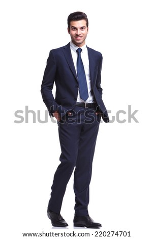 Handsome business man holding his hands in pocket while walking on white studio background, looking at the camera - stock photo