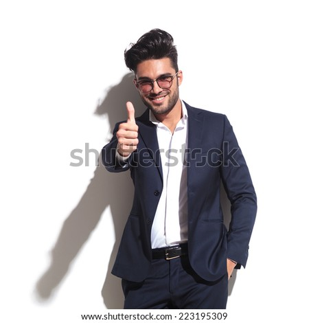 Handsome business man leaning on a white wall while showing thumbs up holding one hand in his pocket. - stock photo