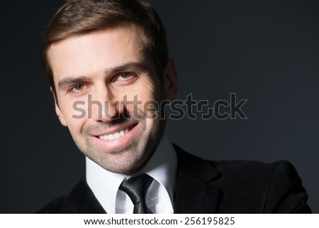 Handsome business man looking happy and smiling - stock photo