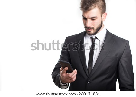 Handsome business man reading an SMS on smartphone against white background