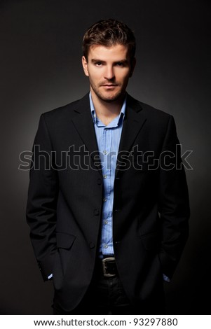 handsome business man standing with hands in pockets against dark background