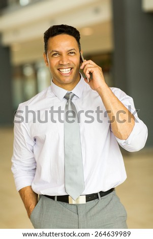 handsome business man talking on mobile phone in office building - stock photo
