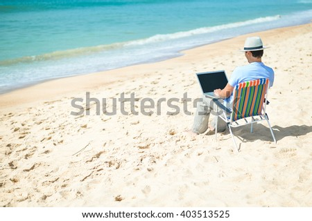 Handsome business man using laptop computer on beach background, back side view outside - stock photo