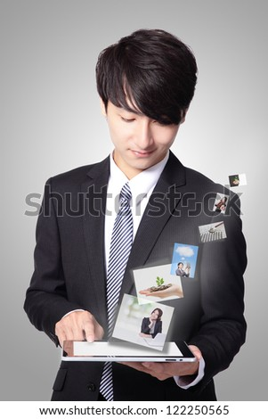 handsome business man using touch screen tablet pc with streaming images, concept for business and cloud computing, asian man model