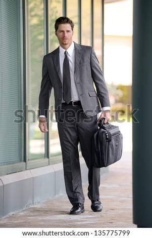 Handsome Business Man Walking Beside a Building - stock photo