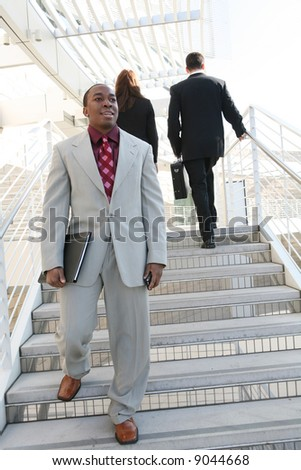 Handsome business man walking down the stairs - stock photo