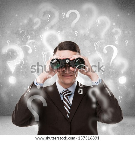 Handsome business man with binoculars and question marks above his head - stock photo