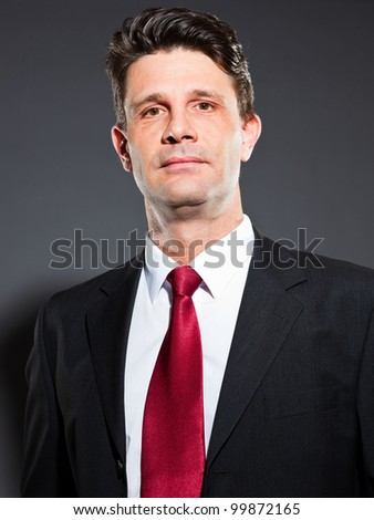 Handsome business man with blue suit and red tie isolated on dark background. Serious looking. Studio shot. - stock photo