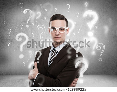 Handsome business man with question marks above his head - stock photo
