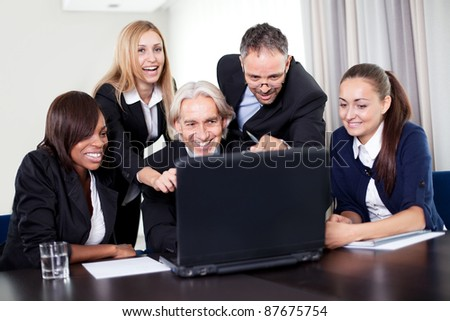 Handsome business manager showing a presentation on his laptop to the team at a meeting - stock photo