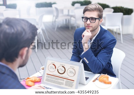 Handsome business partners have discussion in cafe - stock photo