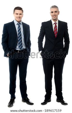 Handsome business partners posing with hands in pockets - stock photo