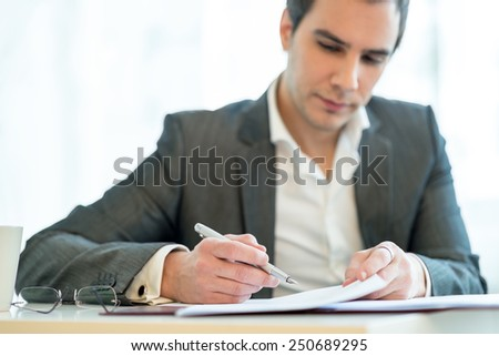 Handsome businessman analysing a report making notes with his pen on the paperwork, close up facing camera. - stock photo