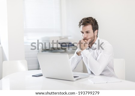 handsome businessman at office in front his laptop - stock photo