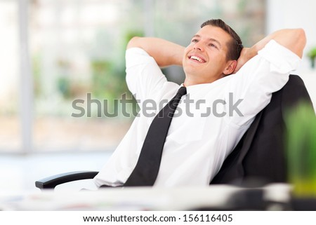 handsome businessman daydreaming in his office - stock photo