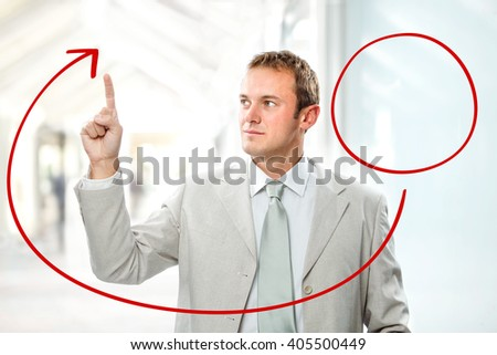 handsome businessman draw chart with hand at office - stock photo