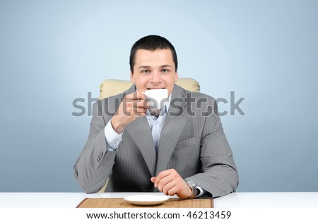 Handsome businessman drinking coffee, on blue background - stock photo