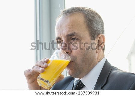 Handsome businessman drinking orange juice.