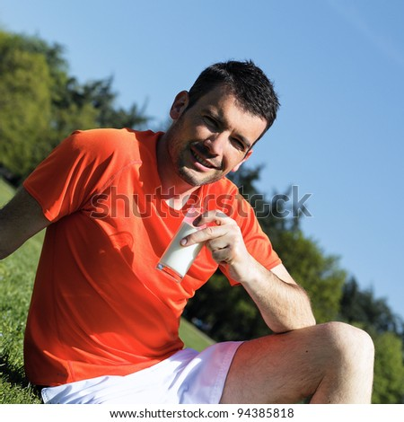 handsome businessman drinking water in blue sky - stock photo