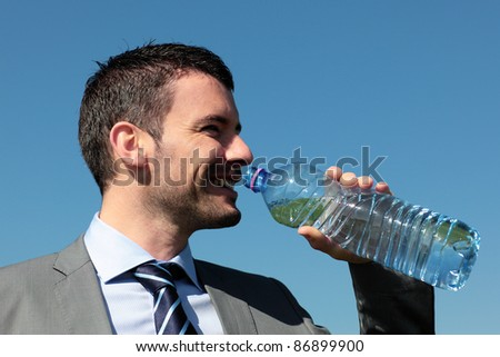 handsome businessman drinking water with bottle in blue sky - stock photo