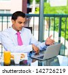 Handsome businessman eating breakfast and shocked and upset at what he see on his laptop screen, isolated on city background - stock photo