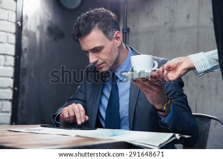 Handsome businessman getting his coffee while reading news in cafe - stock photo