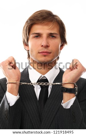 Handsome businessman hands in handcuffs over a white background - stock photo