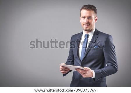 Handsome businessman holding a digital tablet on grey background - stock photo