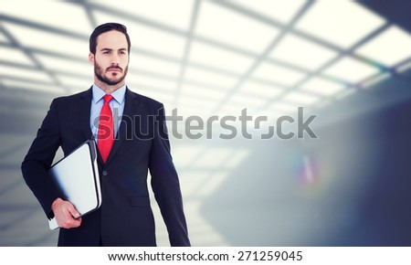 Handsome businessman holding briefcase and laptop against white room with windows at ceiling - stock photo