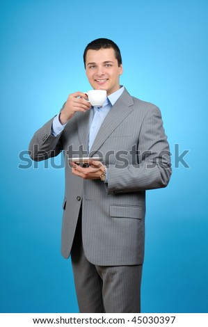 Handsome businessman holding cup of coffee on blue background - stock photo