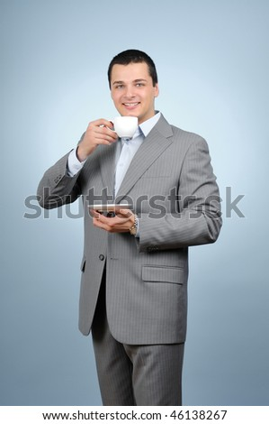 Handsome businessman holding cup of coffee on gray background