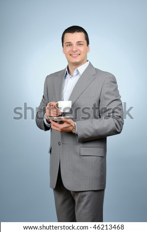 Handsome businessman holding cup of tea gray background
