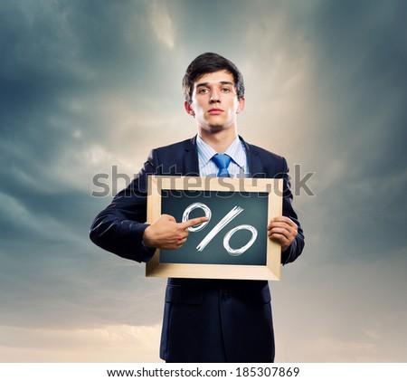 Handsome businessman holding frame with percentage symbol - stock photo