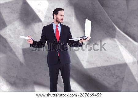 Handsome businessman holding his laptop against grey angular background - stock photo