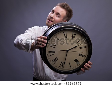 Handsome businessman holding the clock. - stock photo