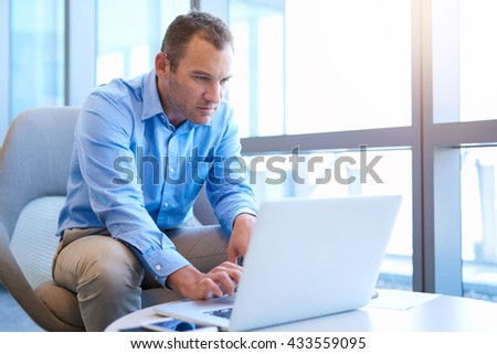 Handsome businessman in a bright modern office with large windows, sitting at a coffee table while on break and looking seriously at some information on his laptop - stock photo