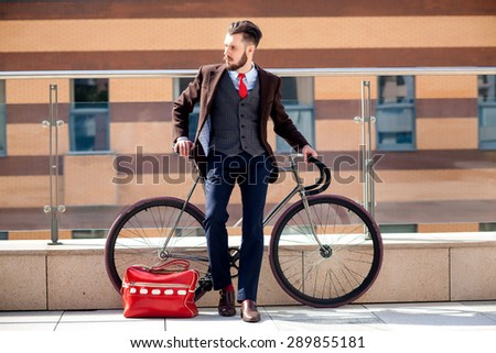 Handsome businessman in a jacket and red tie and his bicycle on city streets. red bag lies next. The concept of the modern lifestyle of young men - stock photo