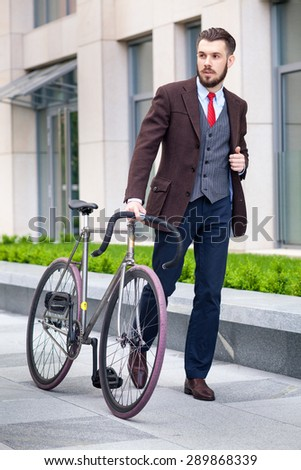 Handsome businessman in a jacket and red tie and his bicycle on city streets. The concept of the modern lifestyle of young men - stock photo