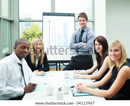 Handsome businessman in a meeting with his colleagues smiling at the camera - stock photo