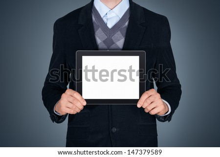 Handsome businessman in black suit showing modern digital tablet with blank screen. Studio shot. Isolated on dark gray background - stock photo