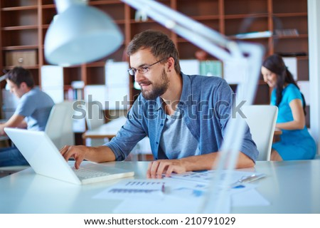 Handsome businessman in casual networking in office - stock photo