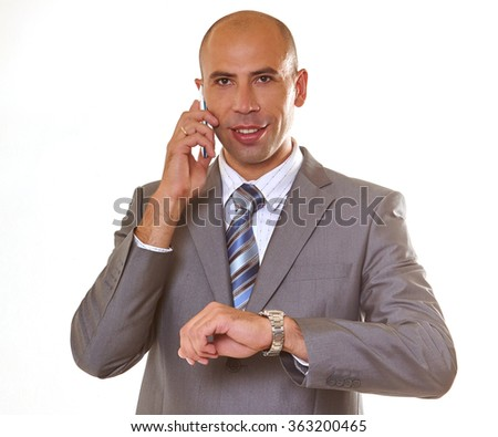 Handsome businessman in  elegant gray suit  speaking on the mobile phone,  he  raised his left hand to consult a watch.  - stock photo