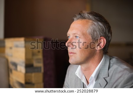 Handsome businessman in grey suit at the cafe - stock photo