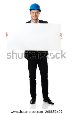 Handsome businessman in hard hat holding empty banner. - stock photo