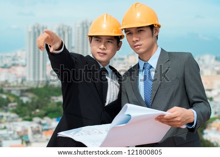 Handsome businessman in hardhat pointing in the direction of a new construction site - stock photo