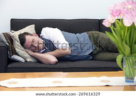 handsome businessman in his 50's sleeping on couch  - stock photo