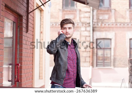 Handsome businessman in leather jacket speaking on the phone  - stock photo