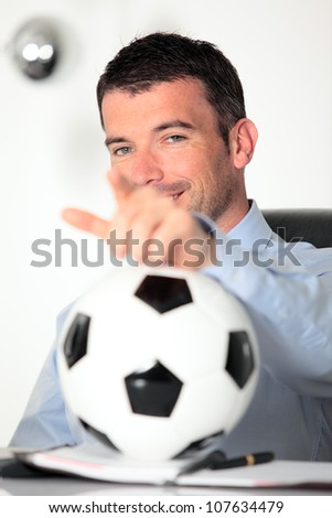handsome businessman in office with computer and ball - stock photo
