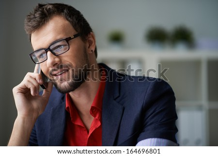 Handsome businessman in smart casual and eyeglasses speaking on the phone - stock photo